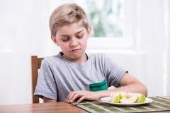 El muchacho no le gusta la fruta foto de archivo libre de regalías