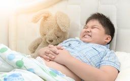 El muchacho obeso en él cama tiene un dolor de estómago imagenes de archivo