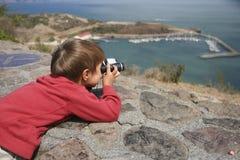 El muchacho observa la visión a través de los prismáticos Foto de archivo