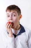 El muchacho oscuro-cabelludo en una camiseta blanca que come una manzana roja Imagen de archivo