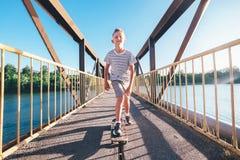 El muchacho patina en tablero del patín en el puente sobre el río Imagen de archivo libre de regalías