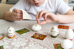 El muchacho pega etiquetas engomadas en los huevos de Pascua Fotografía de archivo