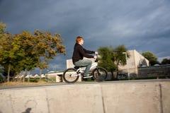 El muchacho pelirrojo de Joung está saltando con su bici de BMX Fotos de archivo libres de regalías
