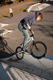 El muchacho pelirrojo de Joung salta con su bici de BMX en el parque del patín Imagen de archivo