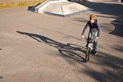 El muchacho pelirrojo de Joung salta con su bici de BMX en el parque del patín Imagen de archivo libre de regalías