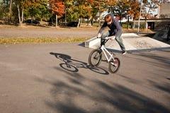 El muchacho pelirrojo de Joung salta con su bici de BMX en el parque del patín Fotos de archivo libres de regalías