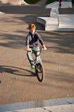 El muchacho pelirrojo de Joung salta con su bici de BMX en el parque del patín Fotografía de archivo