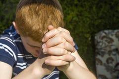 El muchacho pelirrojo joven hace sus manos doblar Foto de archivo libre de regalías
