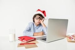 El muchacho pensativo en sombrero de la Navidad está sintiendo cansado Fotografía de archivo