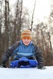 El muchacho piensa el mecanismo impulsor de la colina en invierno en los trineos fotos de archivo