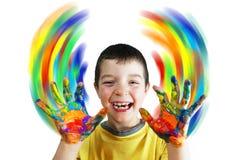 El muchacho pinta círculos de color por las manos Fotografía de archivo