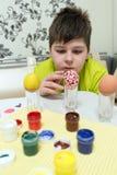 El muchacho pinta los huevos de Pascua con un cepillo Fotografía de archivo libre de regalías