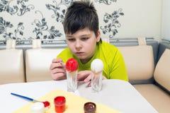 El muchacho pinta los huevos de Pascua con un cepillo Fotografía de archivo
