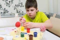 El muchacho pinta los huevos de Pascua con un cepillo Foto de archivo