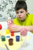 El muchacho pinta los huevos de Pascua con un cepillo Fotos de archivo libres de regalías