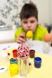El muchacho pinta los huevos de Pascua con un cepillo Imagen de archivo