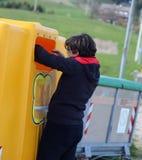 El muchacho pobre mira en el cubo de la basura amarillo en busca de somethin Foto de archivo