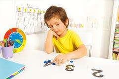El muchacho pone aprende contar con números y valores Foto de archivo