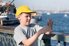 El muchacho pone el cebo en el gancho imagen de archivo libre de regalías