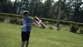 El muchacho pone en marcha un avión del juguete en el parque en el tiempo soleado que tiene un buen humor Cámara lenta metrajes