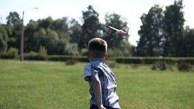 El muchacho pone en marcha un avión del juguete en el parque en el tiempo soleado que tiene un buen humor Cámara lenta HD almacen de metraje de vídeo