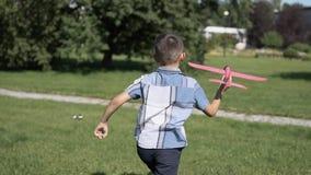 El muchacho pone en marcha un avión del juguete en el parque en el tiempo soleado que tiene un buen humor Cámara lenta Piloto del almacen de video