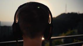 El muchacho pone los auriculares por el mar en la puesta del sol almacen de video