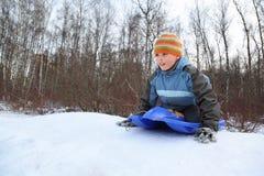 El muchacho por empuje apagado piensa el mecanismo impulsor de la colina en invierno imagen de archivo