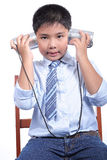 El muchacho precioso escucha teléfono de la lata Imagen de archivo