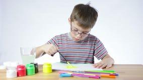 El muchacho preescolar dibuja una imagen de una brocha metrajes