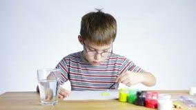 El muchacho preescolar dibuja una imagen de una brocha almacen de metraje de vídeo