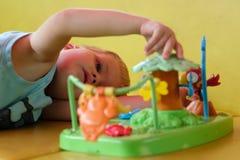 El muchacho preescolar hermoso juega los juguetes en sala de juegos Imagen de archivo