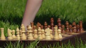 El muchacho puso el pedazo pasado en el tablero de ajedrez y la preparación al juego metrajes