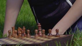 El muchacho puso pedazos de ajedrez en el tablero de ajedrez almacen de video