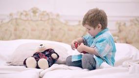 El muchacho puso un despertador para el suyo refiere la cama grande El muchacho está jugando con un despertador en el dormitorio almacen de metraje de vídeo