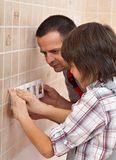 El muchacho que ayuda a su padre instala el panel de delante de wal eléctrico fotografía de archivo