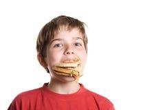 El muchacho que come una hamburguesa. Imagenes de archivo