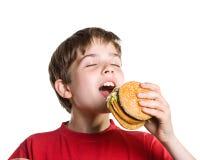 El muchacho que come una hamburguesa. Imagen de archivo libre de regalías