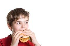 El muchacho que come una hamburguesa. Fotografía de archivo libre de regalías