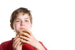 El muchacho que come una hamburguesa. Foto de archivo libre de regalías