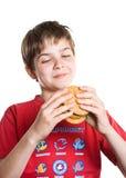 El muchacho que come una hamburguesa. Fotos de archivo