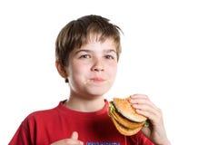 El muchacho que come una hamburguesa. Imagen de archivo