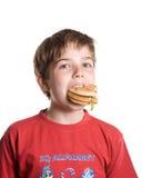 El muchacho que come una hamburguesa. Foto de archivo