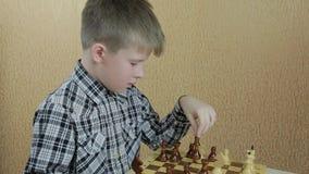 El muchacho que comtempla cuidadosamente su próximo paso en un juego de ajedrez metrajes