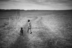 El muchacho que corre con el perro Fotos de archivo