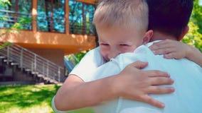 El muchacho que corre a sus brazos del ` s del padre y lo abraza, niño feliz de A encuentra a su padre cerca de la casa almacen de video