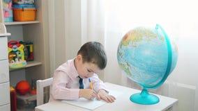 El muchacho que estudia la tierra del planeta y escribe notas en un cuaderno almacen de video