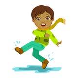 El muchacho que golpea el agua con el pie con el pie, niño en la lluvia de Autumn Clothes In Fall Season Enjoyingn y tiempo lluvi Fotografía de archivo libre de regalías