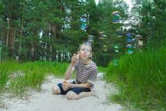 El muchacho que hace burbujas de jabón en las dunas de arena blancas vara en el fondo de la madera de pino Foto de archivo libre de regalías