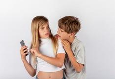 El muchacho que intentaba espiar un teléfono móvil del ` s de la muchacha pero a la muchacha lo notó Imagenes de archivo